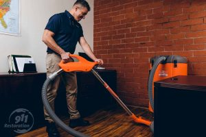 commercial restoration technician vacuuming water