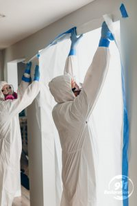 mold removal team taping wall