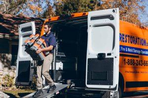 water damage restoration technician taking fans out of truck