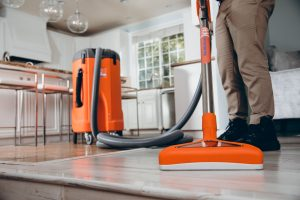 water damage restoration technician vacuuming water in residence